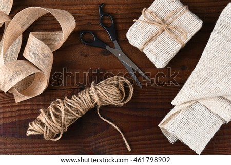 Top view of the tools for wrapping Christmas presents with burlap fabric and ribbon with scissors and twine on a dark wood surface.
