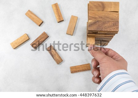 Top view of the tower stack from wooden blocks toy and man's hand take one block - stock photo