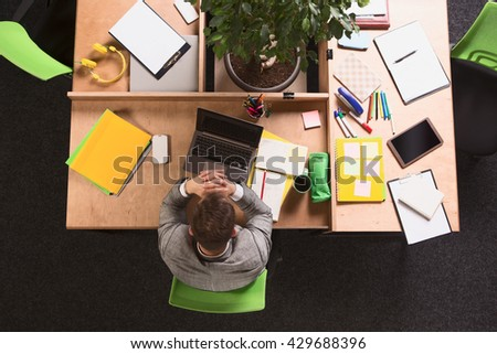 Top view of thoughtful businessman working in office. Handsome sitting in front of laptop computer and thinking about business projects. - stock photo