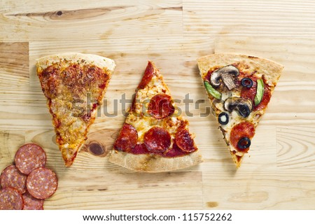 Top view of three baked pizza pie with slices of ham over wooden surface - stock photo