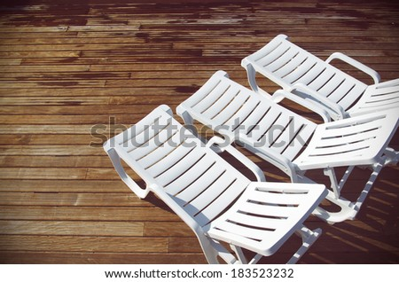 Top view of three empty white deck chairs in a swimming pool deck - stock photo