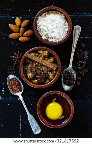 Top view of three wooden bowls with ingredients for baking cake (flour, egg, brown sugar) on dark vintage background.  - stock photo