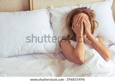 Top view of tired beautiful girl covering her face while lying in bed
