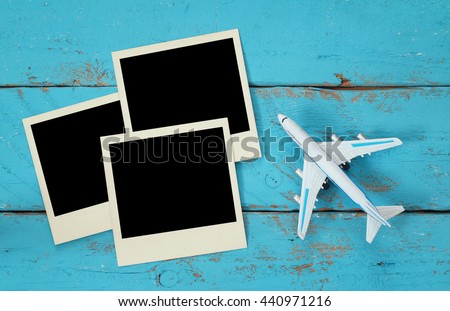 Top view of travel instant photographs next to airplane over wooden table. traveling concept. ready to put images