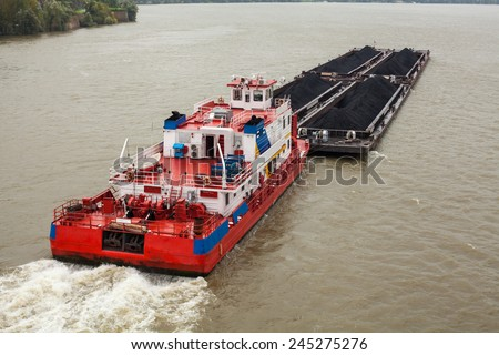 Top view of Tugboat pushing a heavy barge on the river - stock photo