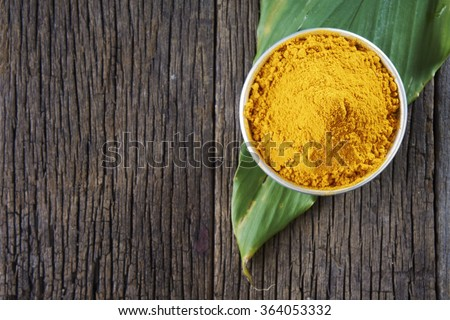 top view of turmeric powder and leaf on the wooden background - stock photo