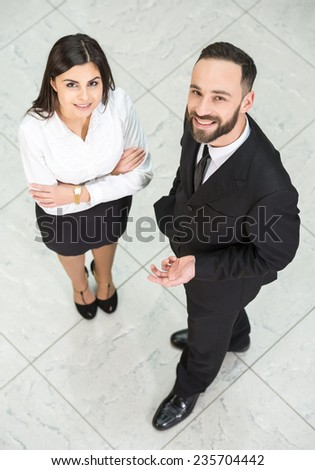 Top view of two business people at work are looking at the camera. - stock photo