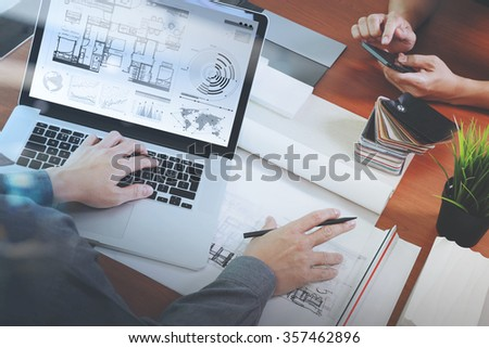top view of two colleagues interior designers discussing data with new modern computer laptop and pro digital tablet with sample material on wooden desk as concept - stock photo