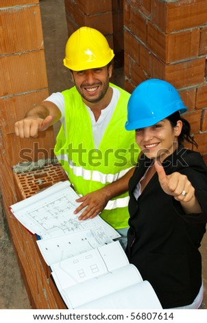 Top view of two happy architect team  on site giving thumbs up - stock photo