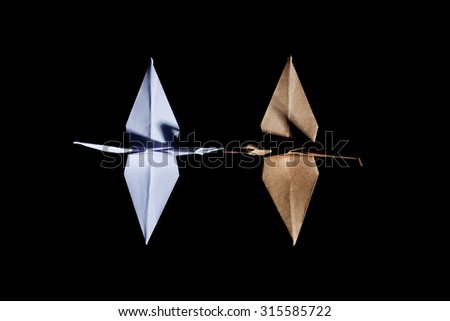 Top view of two origami cranes made from white and brown recycle paper on black background - stock photo