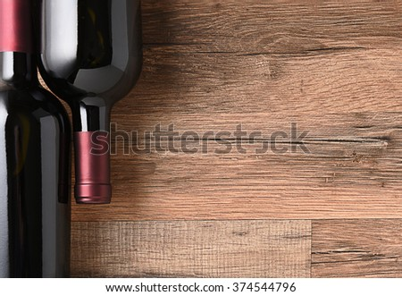 Top view of two wine bottles on a rustic wood table with copy space. - stock photo