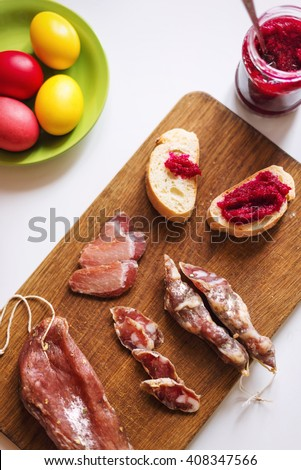 Top view of various meats on serving board. Ham, pork, beef, easter eggs and homemade bread with beetroot-horseradish spread. Preparing for dinner to celebrate Easter. Selective focus - stock photo
