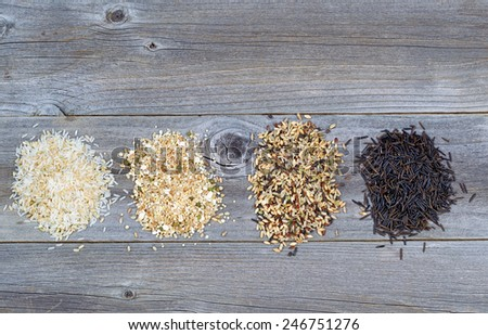 Top view of various rice types each within an individual pile on rustic wood - stock photo