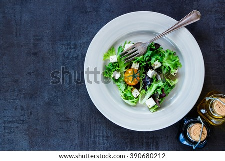 Top view of vegetable colorful salad with yellow tomatoes and feta cheese on vintage table, border. Dark background with space for text. - stock photo