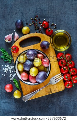 Top view of vintage cutting board with organic ingredients (potatoes, tomatoes, garlic and olive oil) over dark grunge background, top view. Raw vegetables from garden for healthy cooking. - stock photo