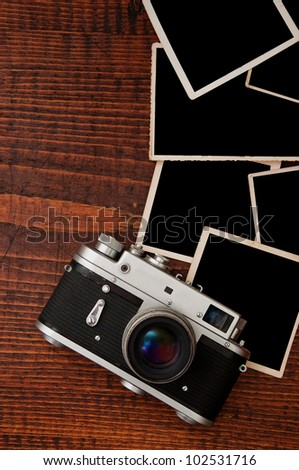 Top View of Vintage photo camera on wooden table plate with blank photo frames - stock photo