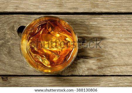 top view of whiskey on the rocks on desaturated weathered wood