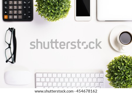 Top view of white desktop with glasses, calculator, plants, smartphone, coffee cup, computer keyboard and other items. Mock up - stock photo