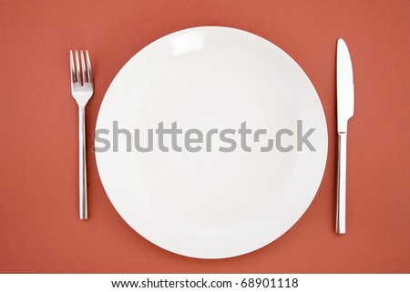 top view of white plate, fork and knife, restaurant tableware - stock photo