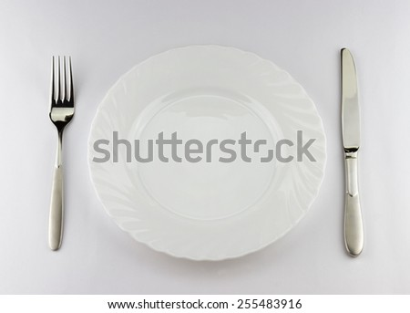 Top view of white plate with silver fork and knife with place for your object - stock photo