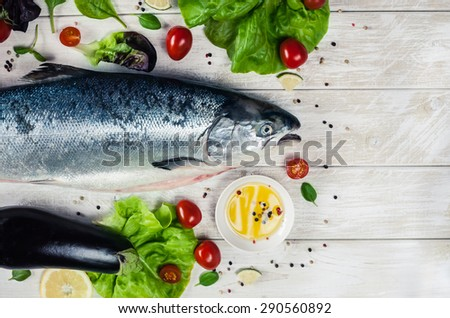 Top view of whole Atlantic salmon with aromatic herbs, spices and lemon. Top view seafood photo with place for your text. Vegetarian or paleo food concept. 