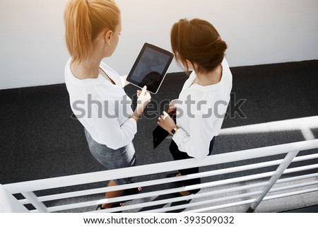 Top view of woman CEO is holding touch pad with mock up copy space on the screen, while is standing with client in corridor company. Two female are watching video on digital tablet before conference - stock photo