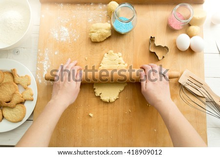 Top view of woman rolling dough for cookies with wooden rolling pin - stock photo