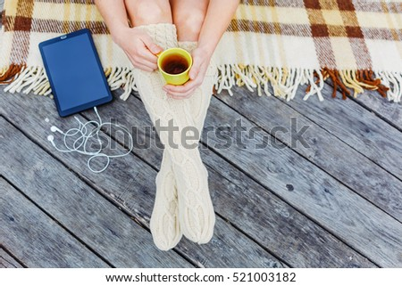 Top view of woman's legs with tablet and coffee cup