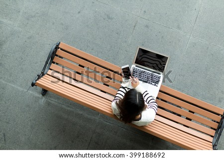 Top view of woman use of cellphone and laptop computer - stock photo