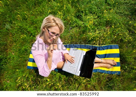 Top view of woman with laptop sitting on blanket - stock photo