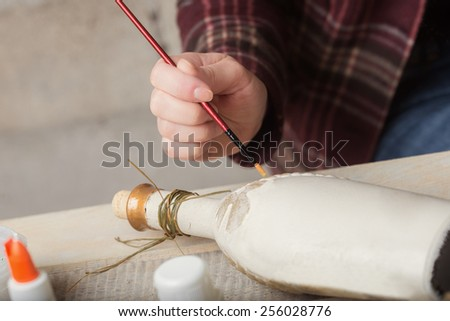 Top view of  women's hand during  handcrafting a decorative bottle - stock photo