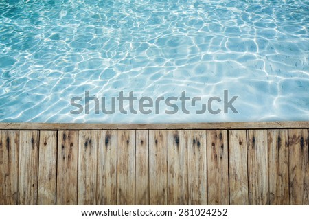 Top view of wood floor or terrace beside the blue crystal clear water. There are little fishes in water.   - stock photo