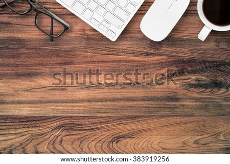 Top view of wood office table with eye glasses, computer keyboard, mouse and a cup of coffee. Top view with copy space. - stock photo