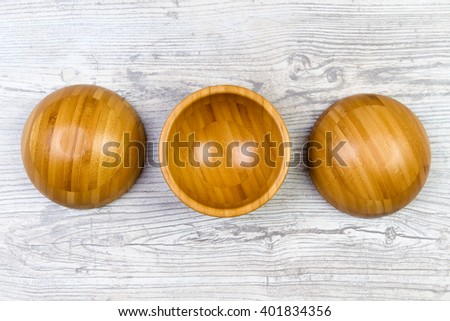 Top view of wooden bowl on weathered wooden background - stock photo