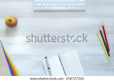 Top view of wooden desk with several color matching items: pencils, booklets and apple. Soft vivid colors, and reduced contrast in order not to distract attention of your project title. - stock photo