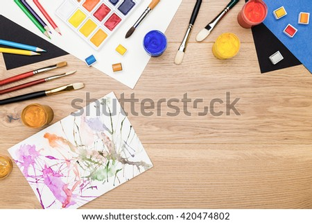 Top view of wooden desktop with drawing tools and abstract painting