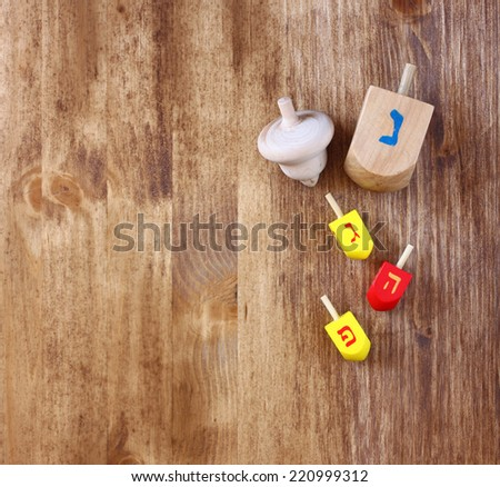top view of wooden dreidels (spinning top) for hanukkah jewish holiday over the table  - stock photo