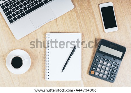 Top view of wooden office desktop with blank cellphone, spiral notepad with pen, coffee cup, calculator and notebook keyboard. Mock up
