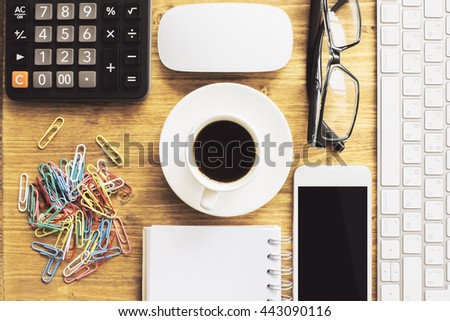 Top view of wooden office desktop with blank smart phone, coffee cup, glasses, computer mouse and keyboard, calculator, clips and spiral notepad. 3D Rendering - stock photo