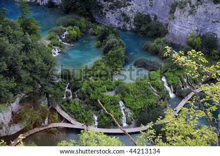 Top view of wooden path across Plitvice Lakes in Croatia, along soft waterfalls. - stock photo