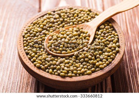Top view of wooden spoon full of green mung beans texture
