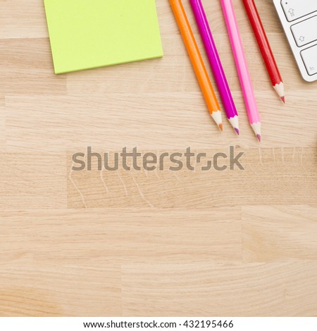 Top view of wooden table with office supplies. Background with copy space. - stock photo