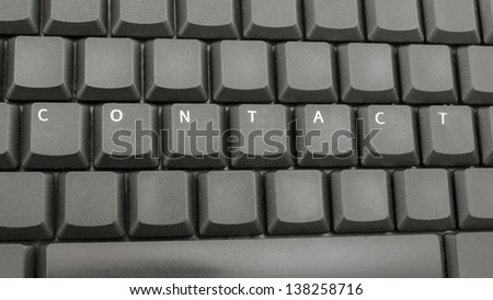 Top view of word contact spelled on computer keyboard.