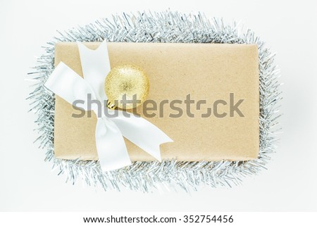 Top view of  Wrapped vintage gift box with white ribbon bow, silver tinsel ornament. Gift for Special Day - stock photo