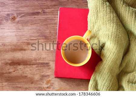 top view of yellow mug with coffee book and blanket  - stock photo