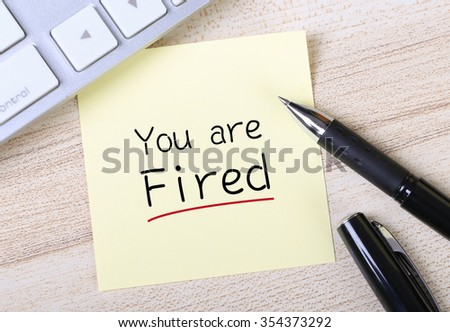 Top view of You Are Fired sticky note pasted on the wooden desk with keyboard and pen aside. - stock photo