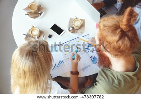 Top view of young ambitious and creative people brainstorming, discussing plans and making notes on paper, developing business strategy for startup project while sitting at table at coffee shop