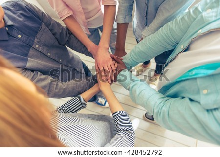 Top view of young business people of different nationalities holding hands together, cropped - stock photo