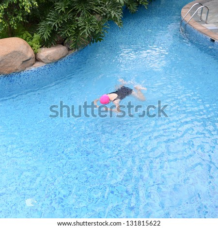 Top view of young woman diving in a swimming pool
