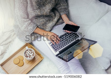 Top view of young woman dressed in pullover sitting on floor and holding laptop while using smartphone.Next cup of cocoa with marshmallows and cookies on tray.Online shopping.Girl chooses gifts online
